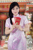 Chinese woman in cheongsam dress giving envelope  — Stock Photo