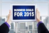 Hands with tablet showing business goals for 2015 — Stock Photo
