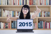 Schoolgirl with laptop showing thumbs-up in library — Stock Photo