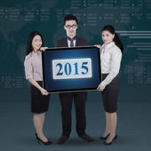 Teamwork holding number 2015 with financial background — Stock Photo