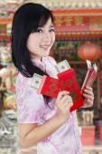 Woman in cheongsam dress holding envelope — Stock Photo