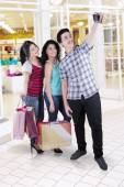 Multiracial group of friends taking photo in mall — Stock Photo