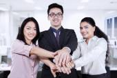 Business team joining hands in the office — Stock Photo