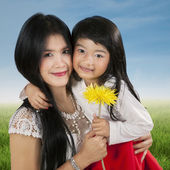 Child holding flower with her parent — Stockfoto