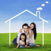 Excited family with a dream house at field — Stock Photo