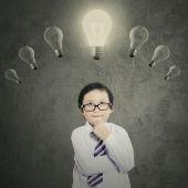 Schoolboy under bright lightbulb — Stock Photo