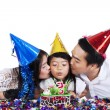 Parents kissing their child in birthday party — Stock Photo #63844075