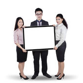 Multi ethnic teamwork holding whiteboard — Stock Photo