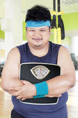Overweight person with scale in fitness center — Stock Photo