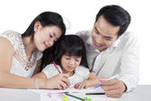 Little girl studying with her parents — Stock Photo