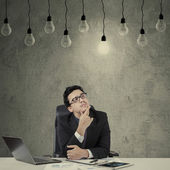 Creative manager looking at lightbulb — Stock Photo