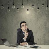 Smart manager looking at illuminated lamp — Stock Photo