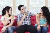 Friends drinking champagne on sofa — Stock Photo