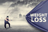 Fat man pulling a weight loss banner — Stock Photo