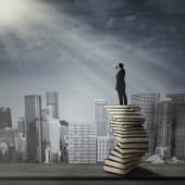 Man standing on a stack of books — Stock Photo