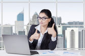 Attractive woman with thumbs up in office — Stock Photo