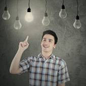 Caucasian person under lightbulb — Stock Photo