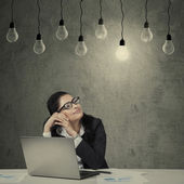 Female employee with laptop looking at lightbulb — Foto de Stock