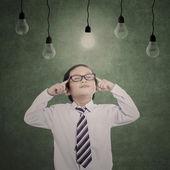 Pensive business child under lit bulbs — Stock Photo