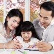 Постер, плакат: Beautiful family doing schools assignment