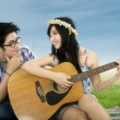 Happy woman playing guitar at field — Stock Photo #67466237