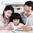 Little girl doing schools task with parents — Zdjęcie stockowe #67466867