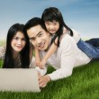 Modern family with laptop on grass — Stock Photo #67469019