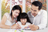 Beautiful family doing schools assignment — Stock Photo