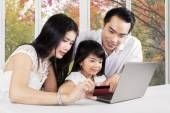 Family with laptop and credit card — Foto de Stock