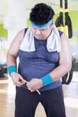 Overweight man measure his belly at gym — Stok fotoğraf