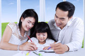 Parents giving homeschooling to their child — Stock Photo