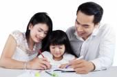 Ung familj studera tillsammans på bord — Stockfoto