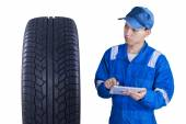 Asian mechanic controls a tire with tablet — Stock Photo