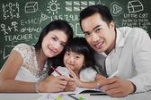 Beautiful family doing schoolwork  — Stock Photo