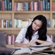 Female student concentrate studying in library — Stock Photo #68171531
