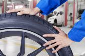 Mechanic hands pushing tire at workshop — Stock Photo