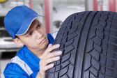 Mechanic checking a textured tire — Stock Photo