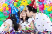 Parents kissing their child in birthday party — Stock Photo