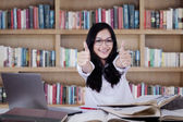Modern girl showing thumbs up in library — Stock Photo