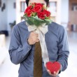 Man holding flowers and gift — Stock Photo #68750891