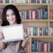 Schoolgirl showing a tablet screen in library — Stock Photo #69868439