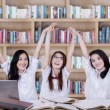 Three schoolgirls raise hands in library — Stock Photo #69868839
