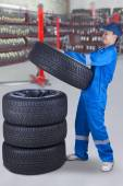 Mechanic piling up tires in the workshop — Stock Photo