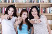 Students pointing at camera in library — Stockfoto