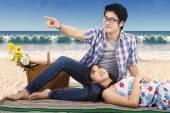 Couple sitting on mat at coast — Stock Photo