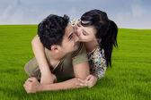 Woman kiss her husband at field — Stock Photo