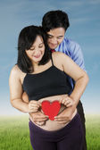 Young parents holding heart symbol — Stock Photo