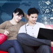 Happy couple sitting on sofa with flying alphabet — Stock Photo #71334535