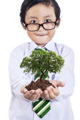 Smiling boy with plant in hands — Stock Photo