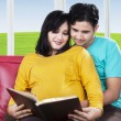 Pregnant woman reading book with husband — Stock Photo #71937743